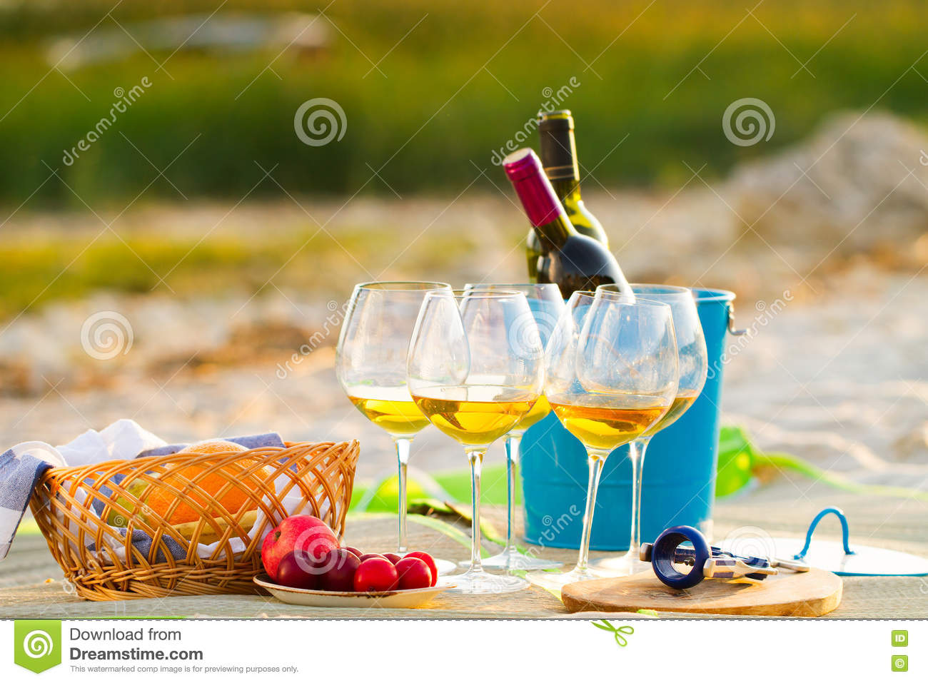 Glasses of the white wine on the beach on sunset, picnic theme,