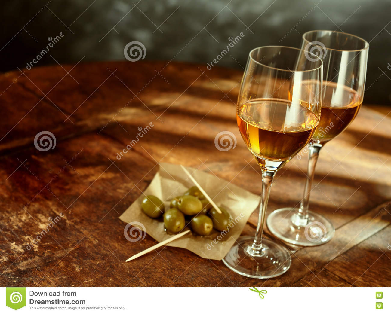 Glasses of Wine on Wood Table with Green Olives