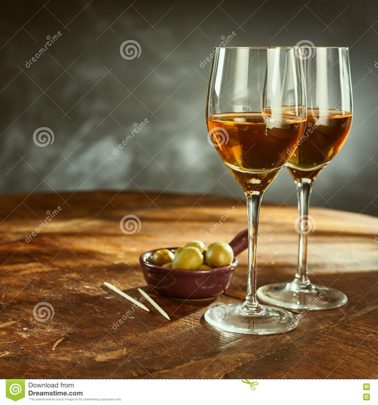 Glasses of Wine on Wooden Table with Green Olives