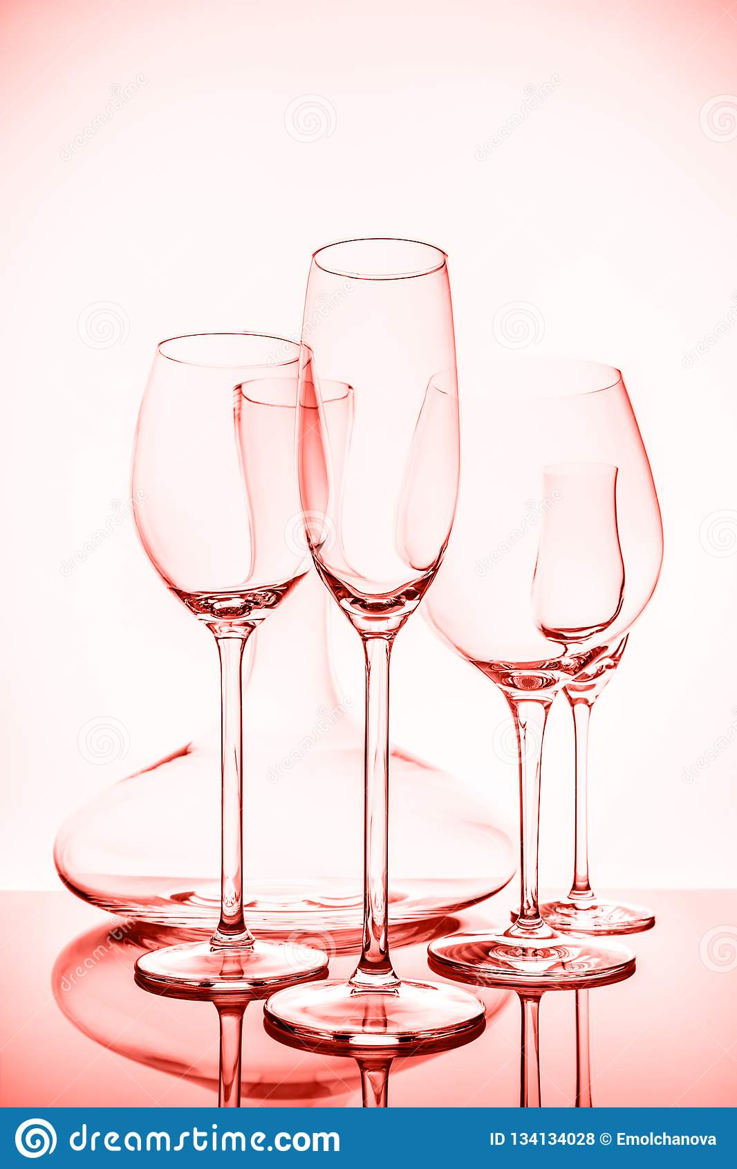 Glassware selection with wine, champagne, liquour glasses and decanter on the light background . Living coral theme - color of the
