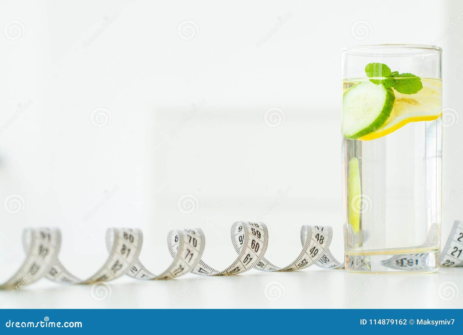 Glaswater met muntbladeren, citroen en komkommer, meetlint -