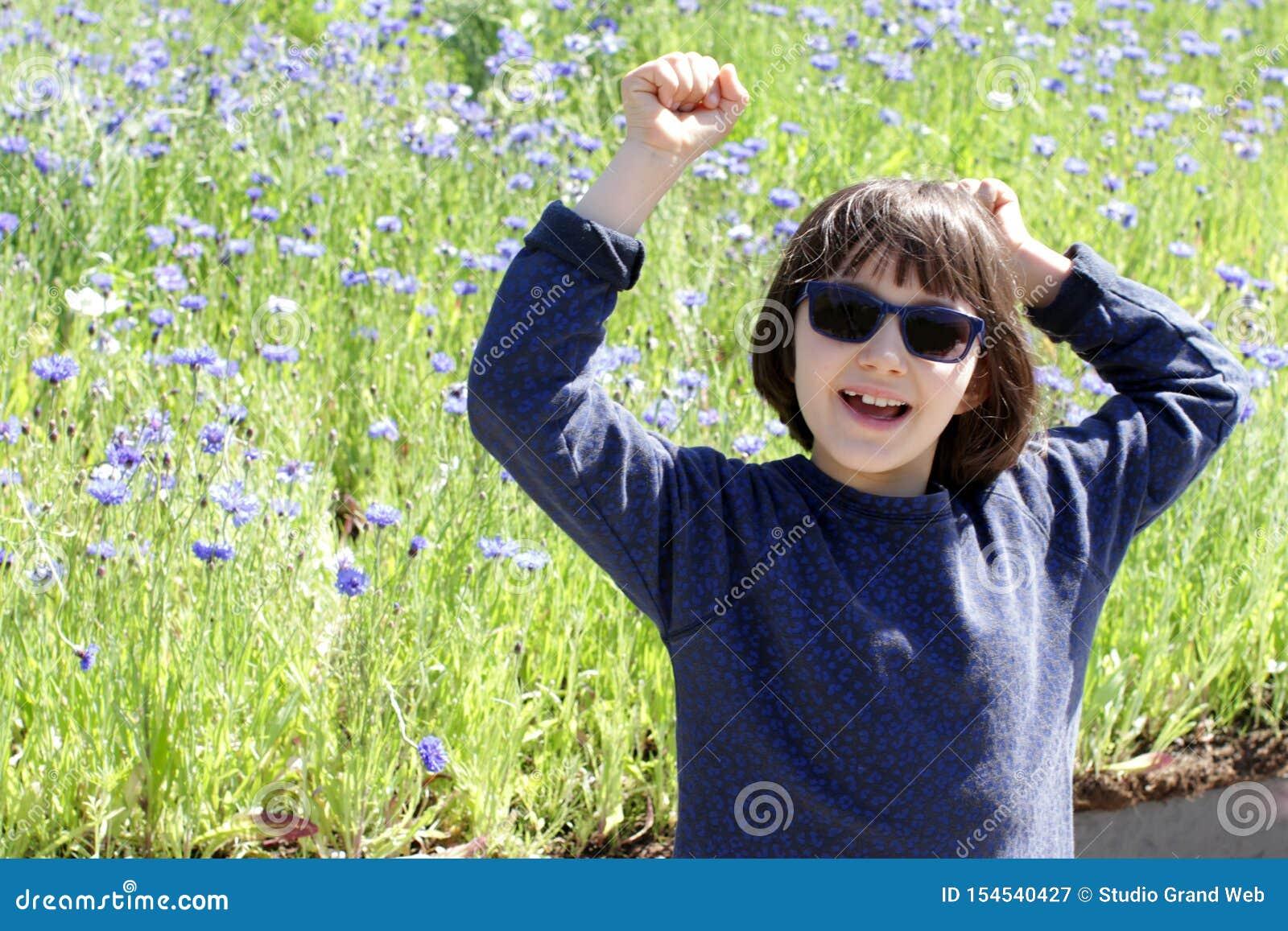 Glat barn med blå solglasögon som skrattar för att vara i natur