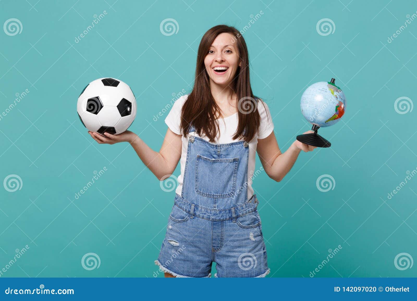 Glat kvinnafotbollsfanjubel stöttar upp det favorit- laget med fotbollbollen, jordvärldsjordklotet som isoleras på blå turkos