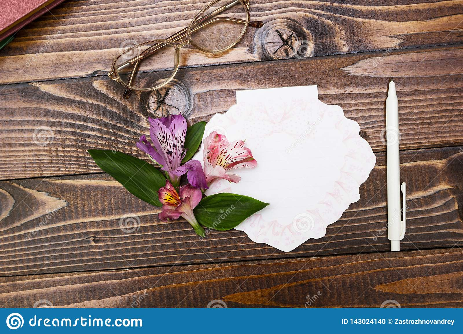 Glazen, notitieboekje en bloemen op houten achtergrond