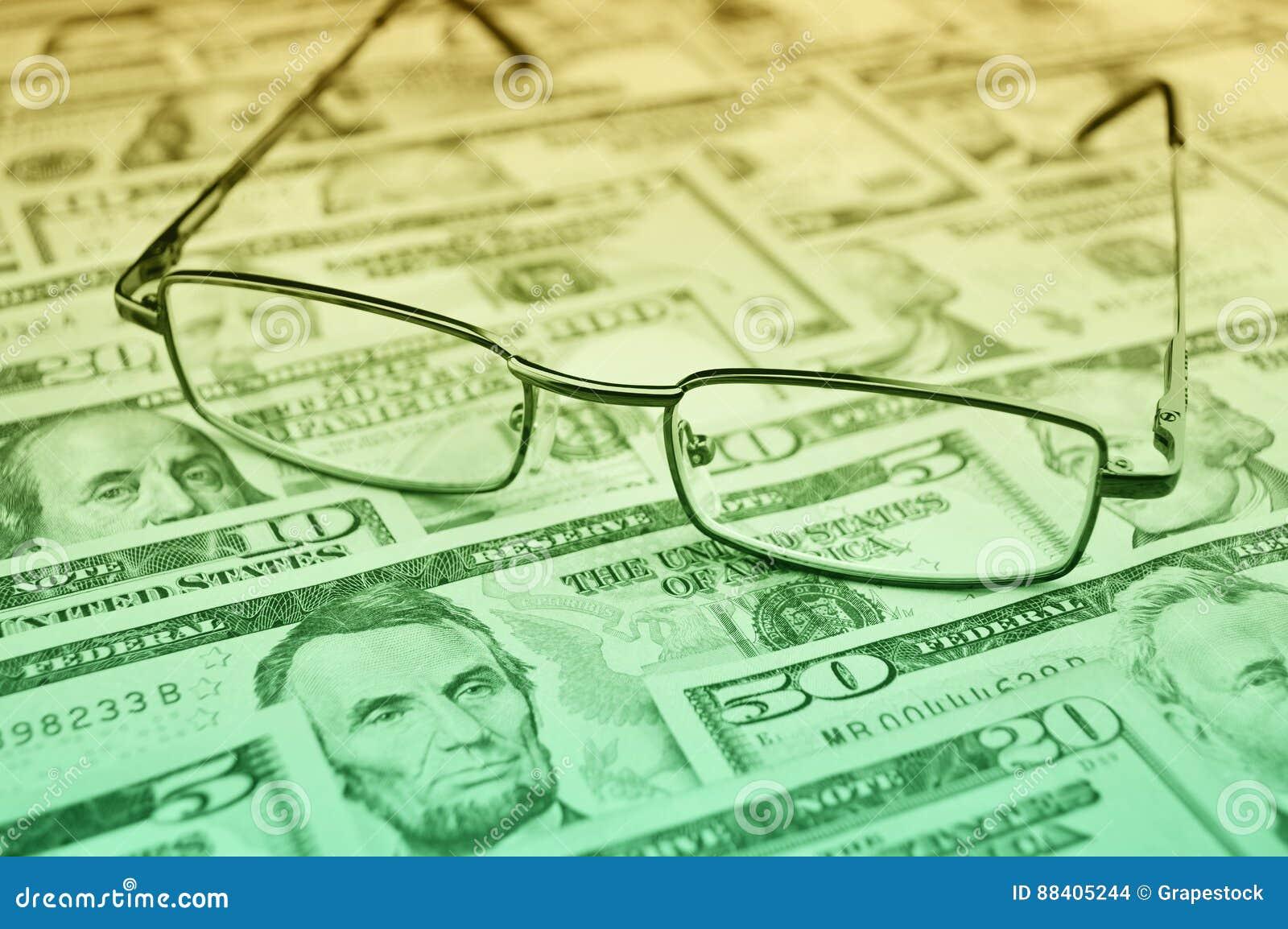 Glazen op dollargeld, financiële en bedrijfsconcept