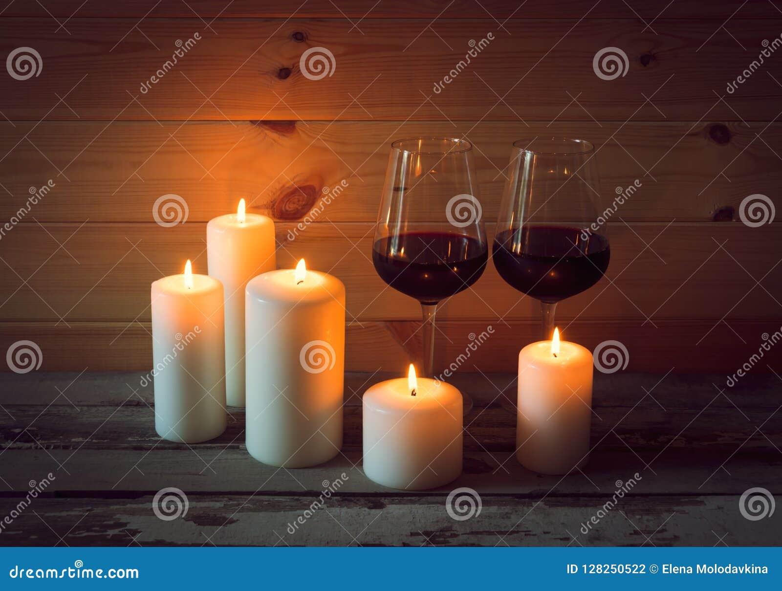 Glazen rode wijn met kaarsen op houten achtergrond