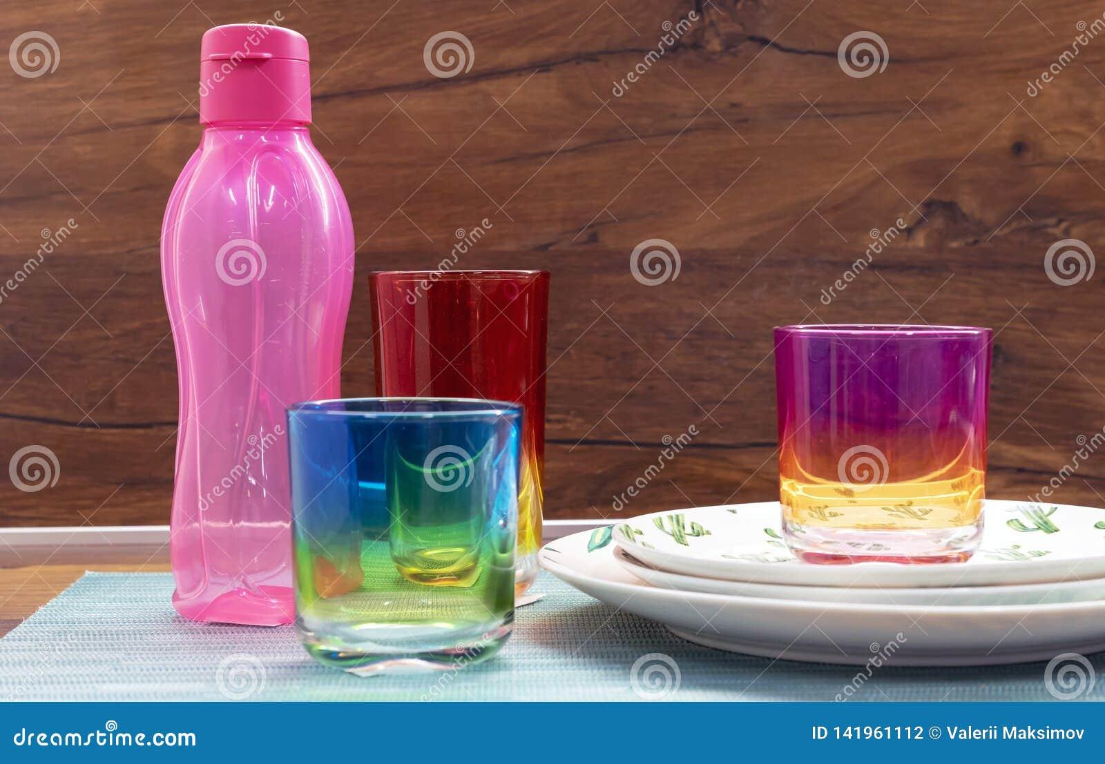 Glazen van multi-colored glas en een roze fles voor koude dranken