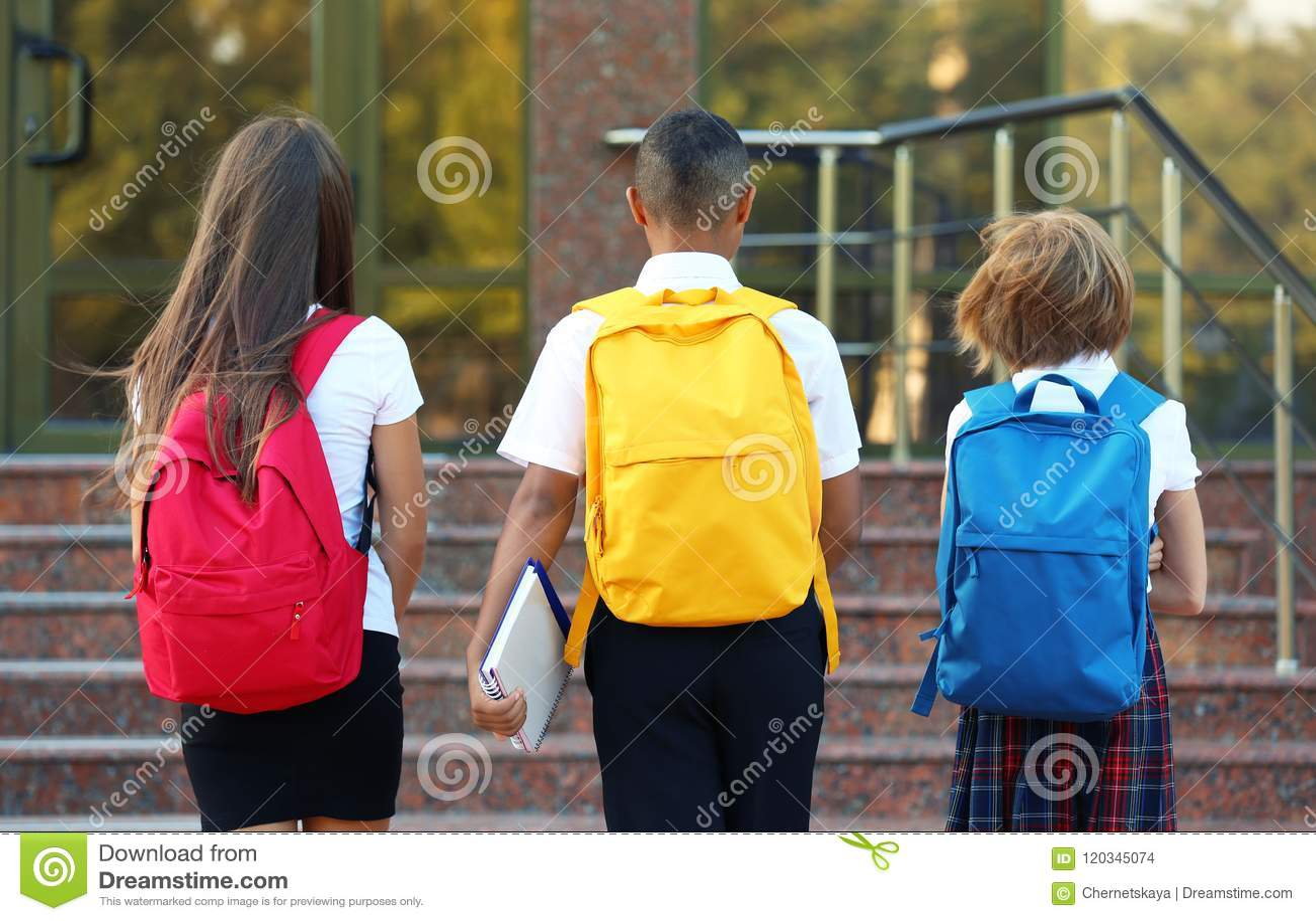 Gli adolescenti con gli zainhi colourful si avvicinano all entrata della scuola