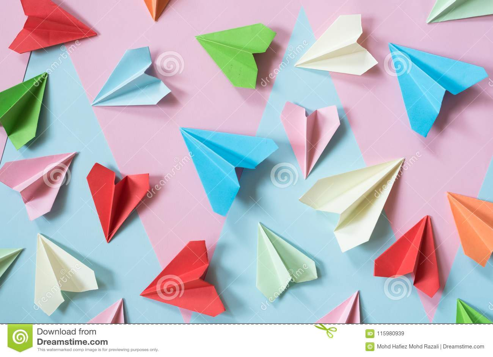 Gli aeroplani di carta variopinti sul rosa pastello e sul blu hanno colorato il fondo