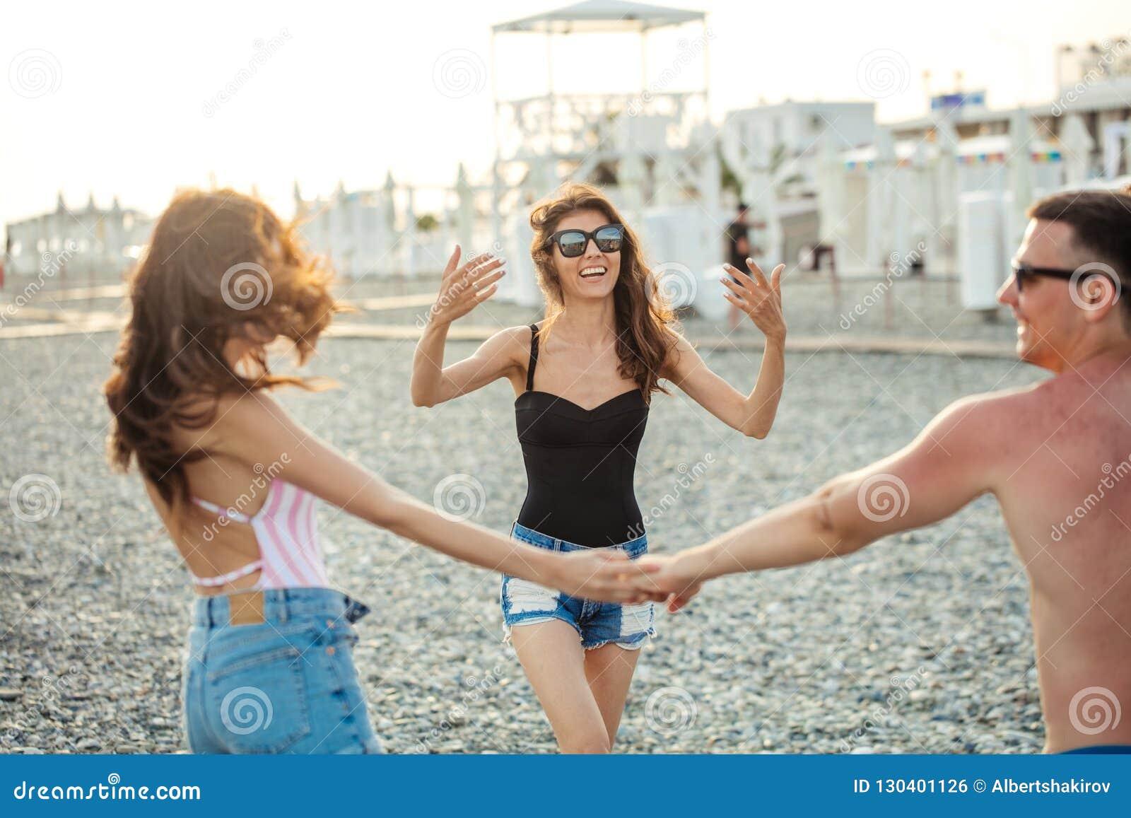 Gli amici ballano sulla spiaggia nell ambito di luce solare del tramonto, divertiresi, felice, godono di