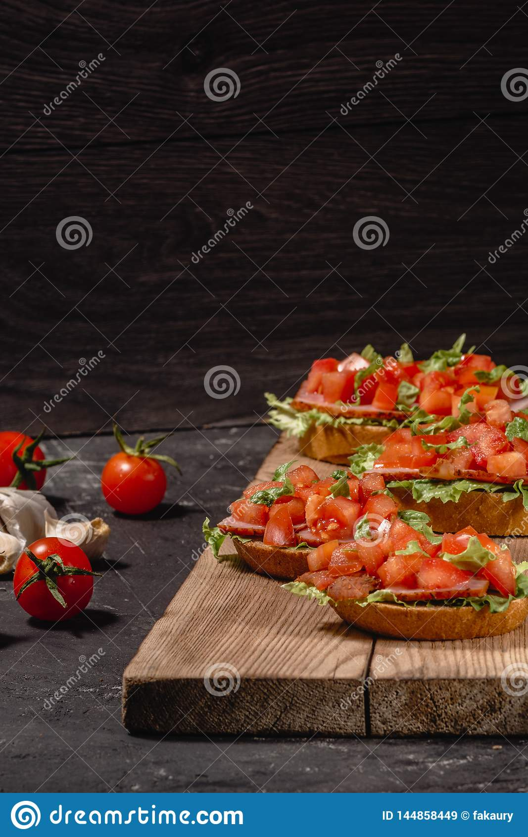 Gli aperitivi italiani del pomodoro saporito saporito, o la Bruschetta, sulle fette di baguette tostate guarnite con le foglie de