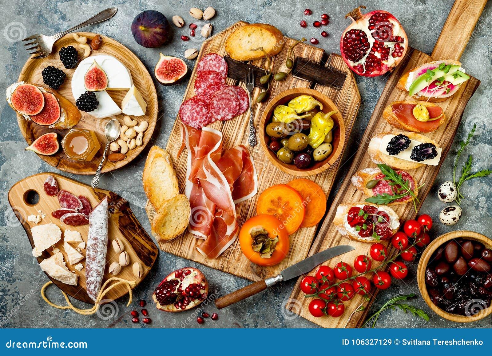 Gli aperitivi presentano con gli spuntini italiani dei antipasti Brushetta o tapas spagnoli tradizionali autentici messi, bordo d