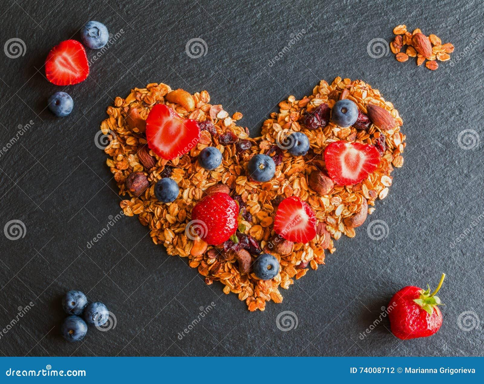 Gli ingredienti nella forma di cuore per cucinare i mirtilli, le fragole ed il granola di una prima colazione fatti dai fiocchi d