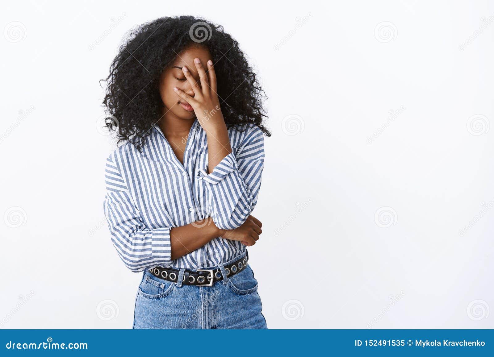 Gli occhi vicini stanchi del bello dell afroamericano facepalm riccio-dai capelli alla moda snobistico della donna hanno importun