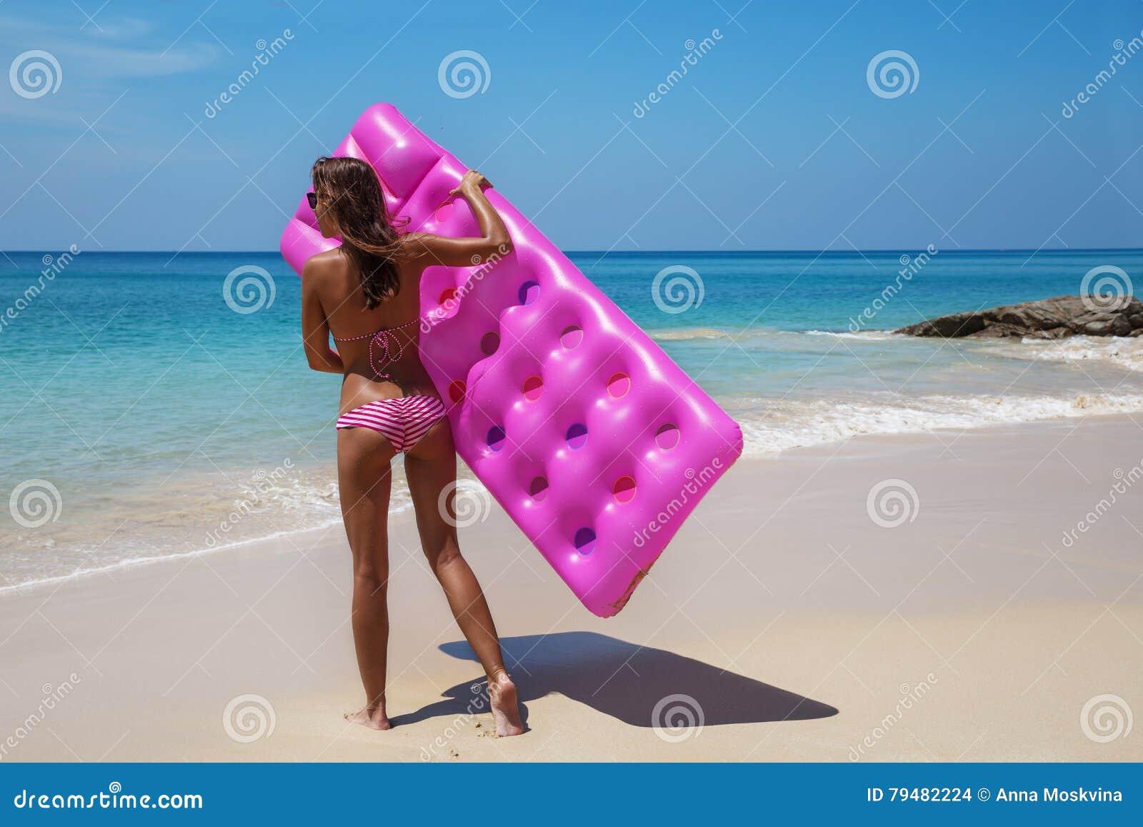 Gli occhiali da sole castana della donna prendono il sole con il materasso di aria sulla spiaggia tropicale