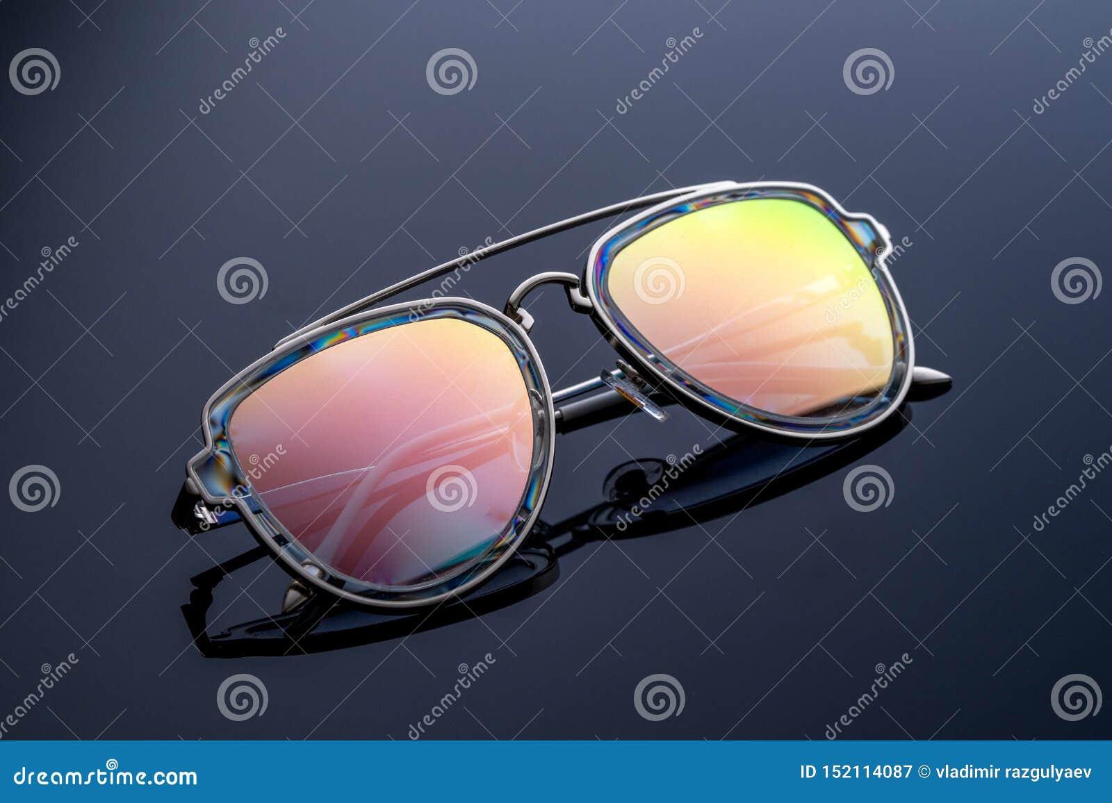 Gli occhiali da sole, colore del camaleonte, luccicano al sole Fondo scuro di pendenza