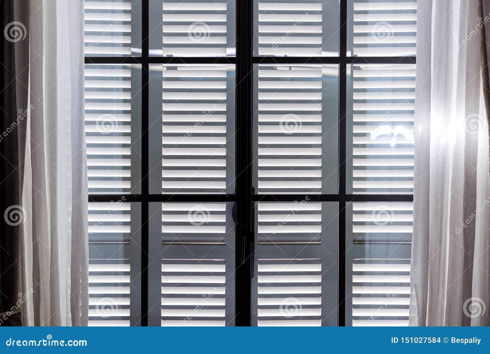 Gli otturatori di legno grigi della finestra
