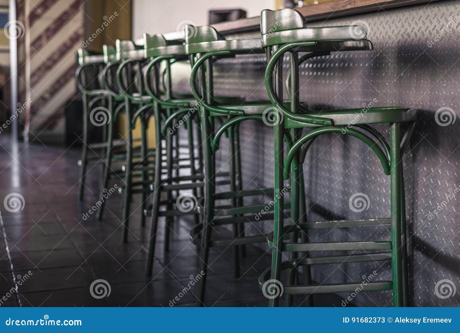 Gli sgabelli da bar verdi dannata stanno in una fila accanto al
