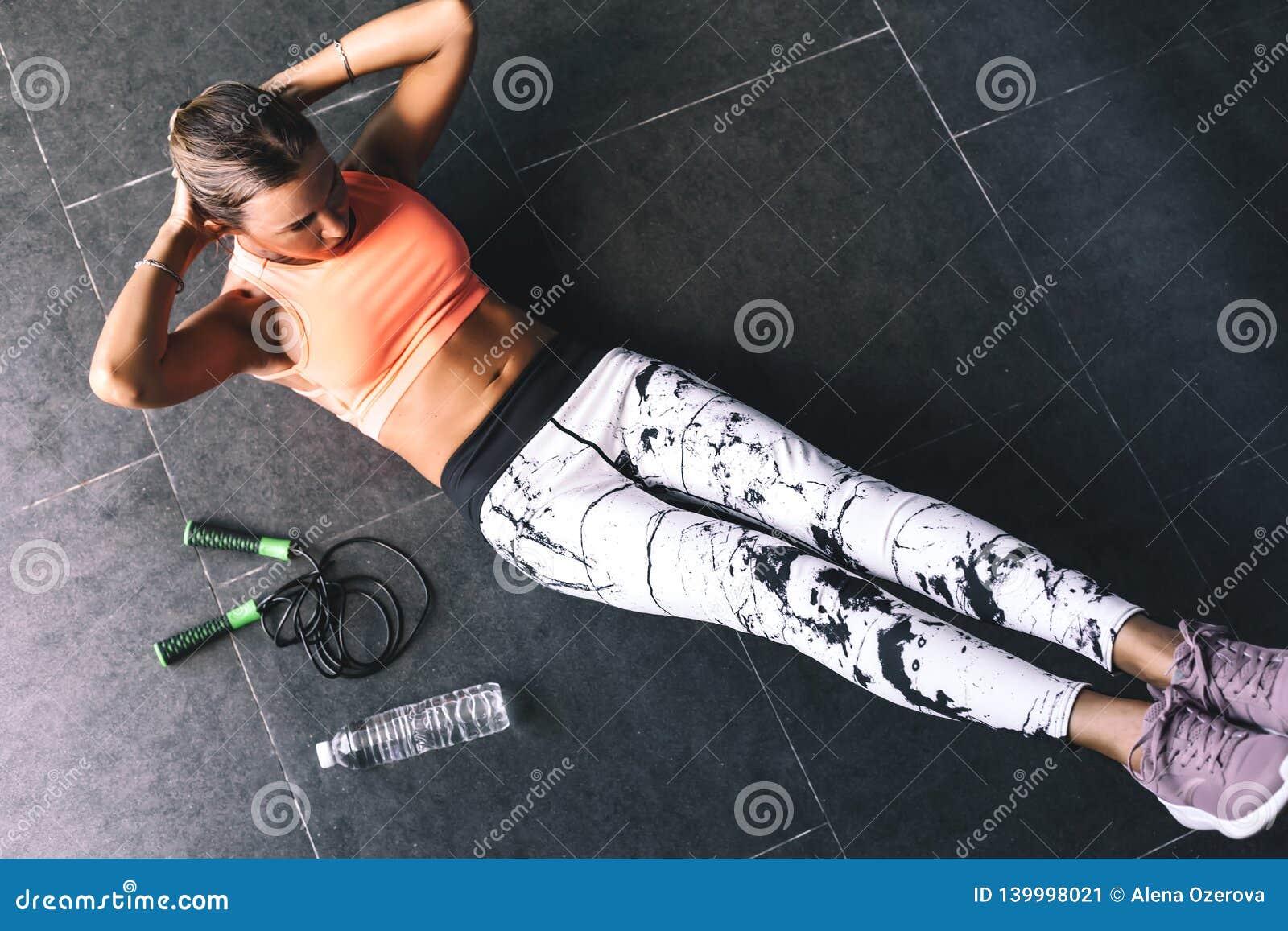 Gli sport d uso di modello di modo indossano fare l esercizio al pavimento nero