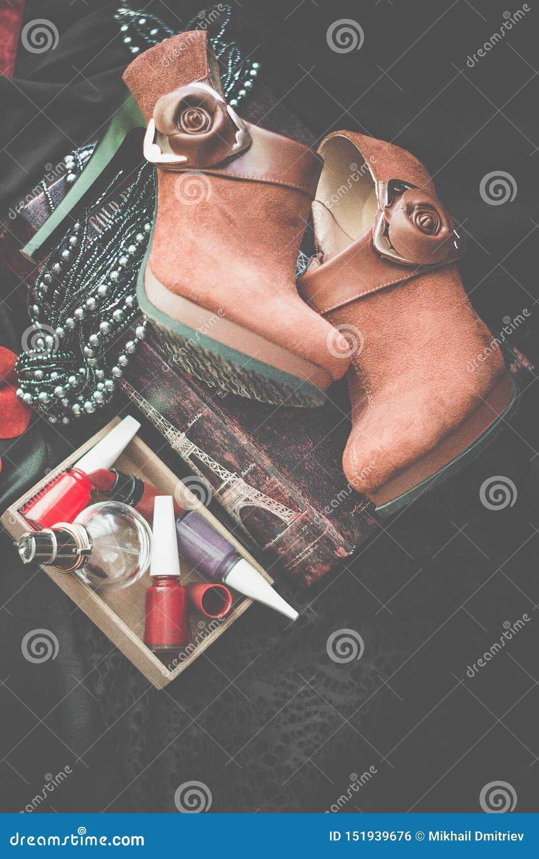 Gli stivali marroni della caviglia della pelle scamosciata si trovano su un fondo scuro Accanto alla scatola con gli accessori de