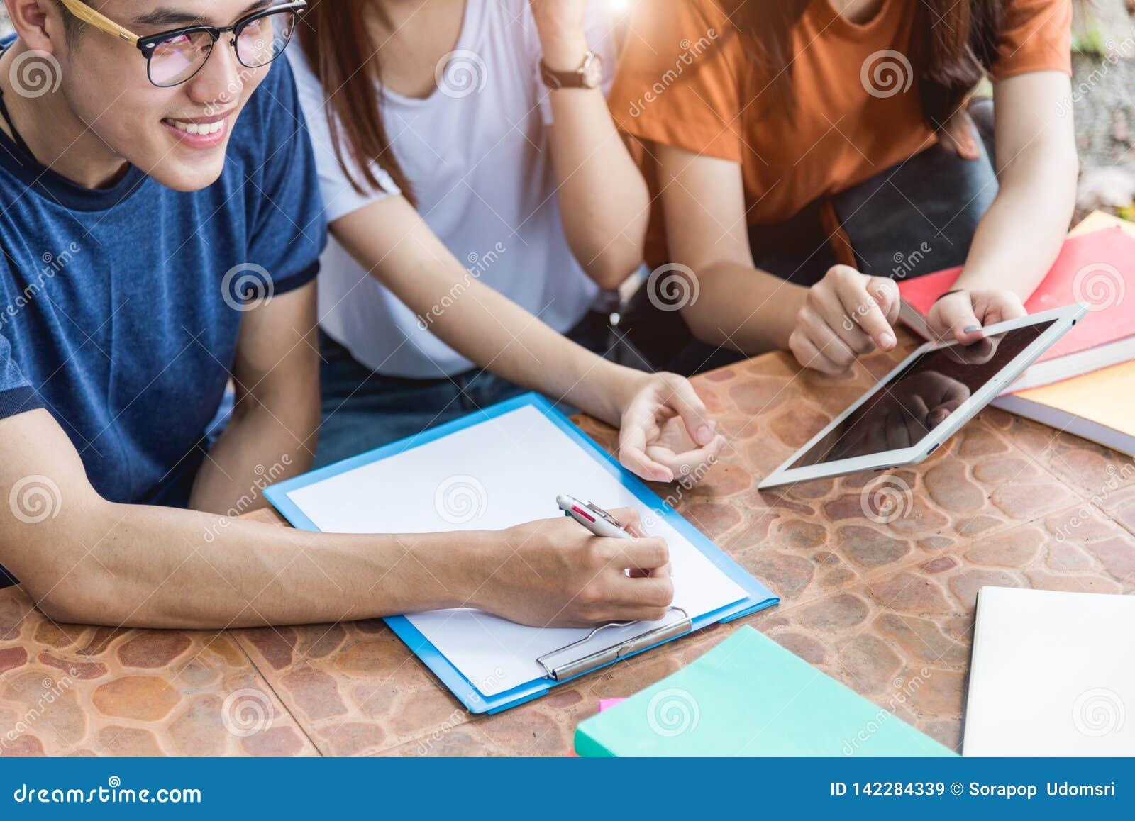 Gli studenti e l amica dell uomo sono consultano le informazioni dal computer portatile, dalla compressa e dal libro del computer