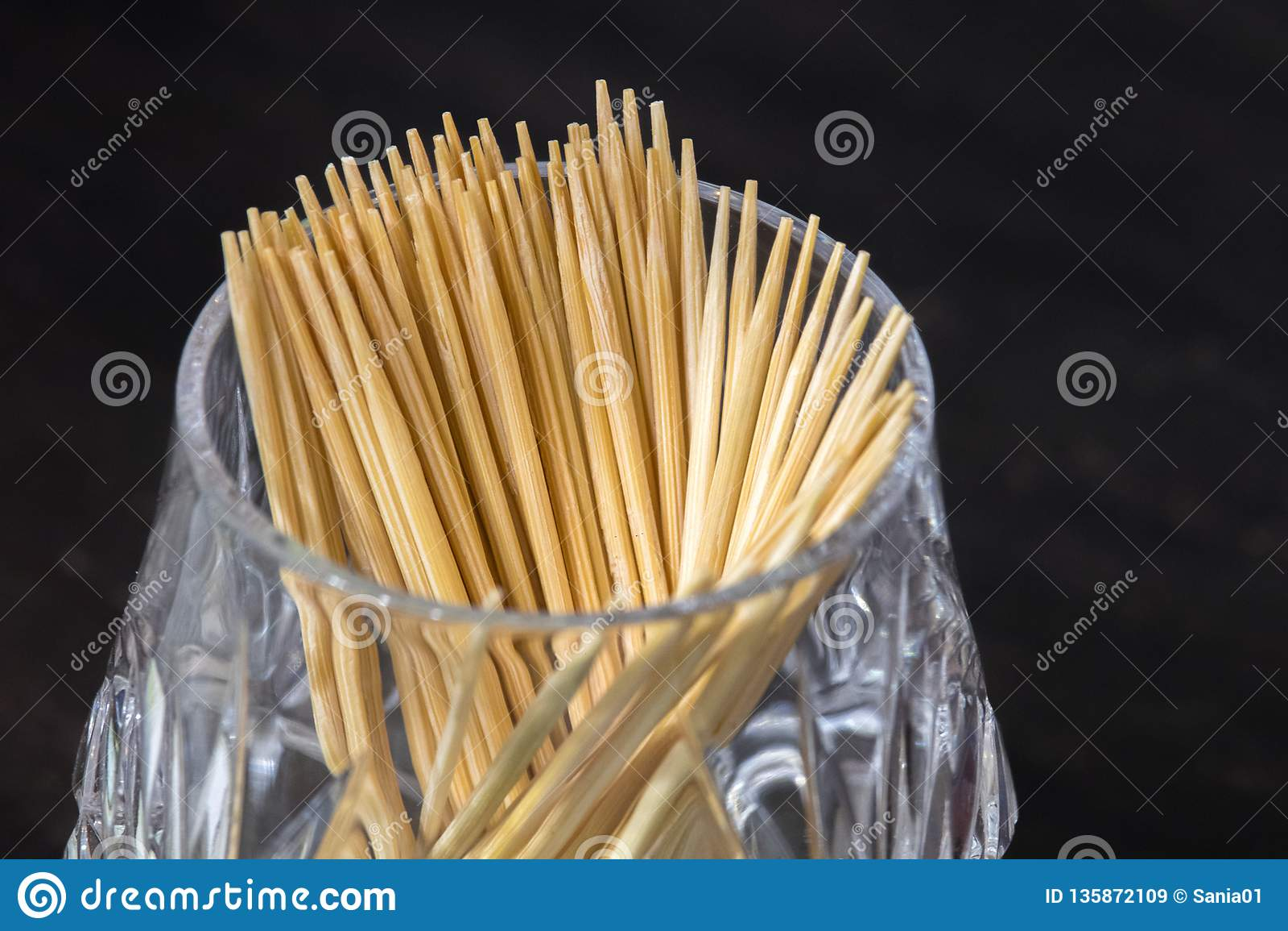 Gli stuzzicadenti di legno in una tazza di vetro sono sulla tavola, su un fondo scuro igiene orale dopo il cibo