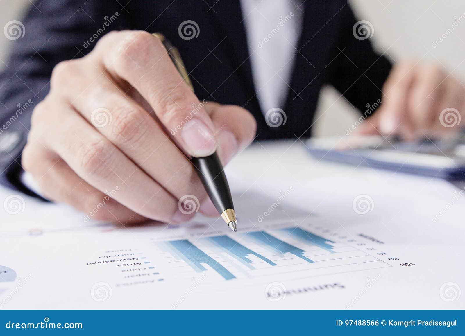 Gli uomini d affari che lavorano con i dati del grafico all ufficio, responsabili di finanza incaricano, affare di concetto ed in