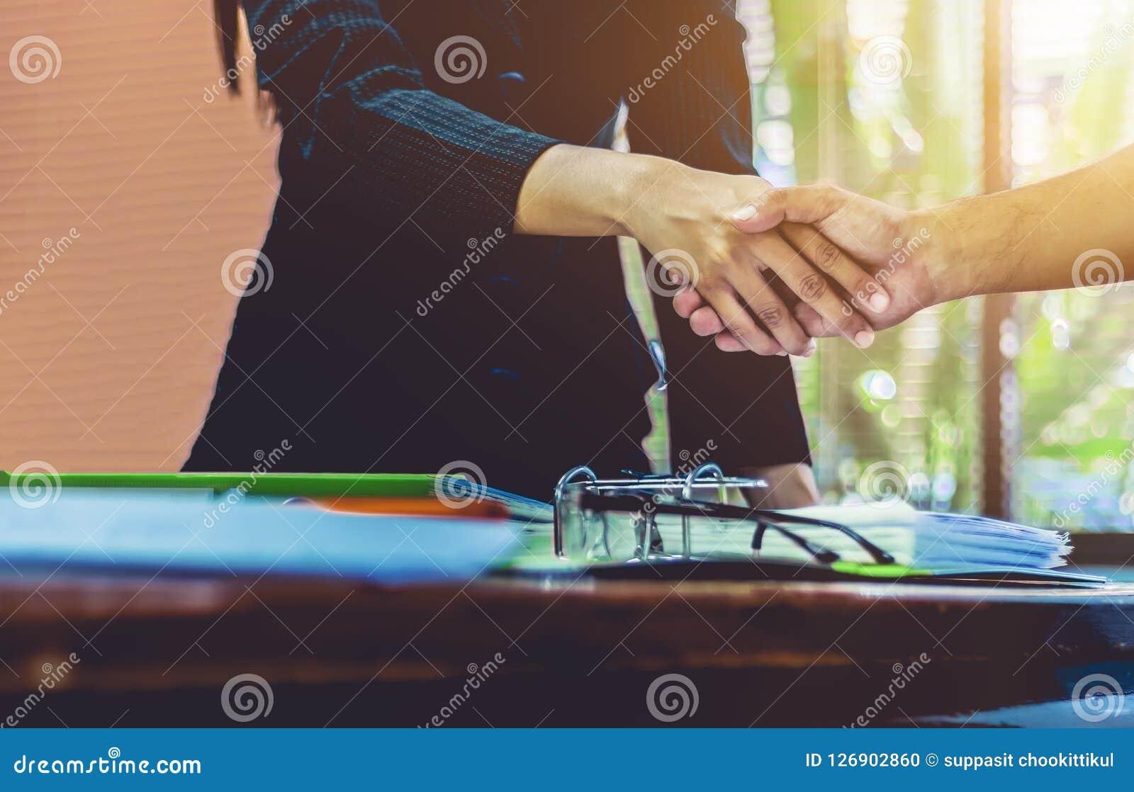 Gli uomini d affari di handshake delle donne di affari riescono a lavoro