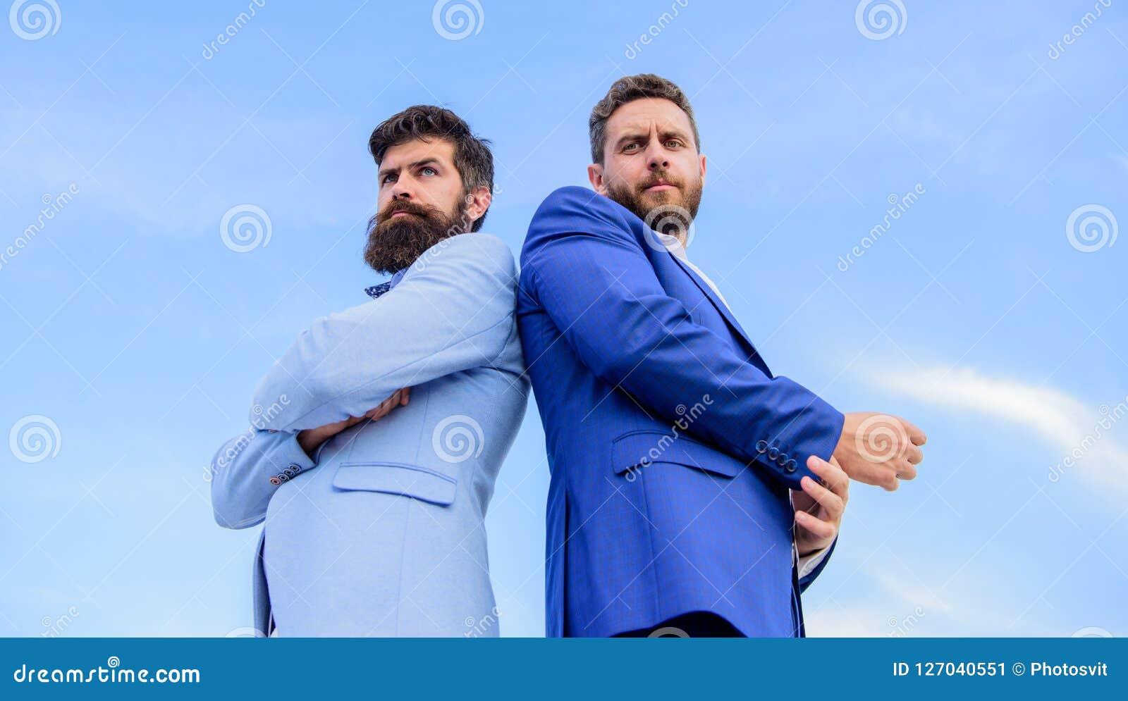 Gli uomini di affari stanno indietro per appoggiare il fondo del cielo blu L aspetto impeccabile migliora l imprenditore del prof