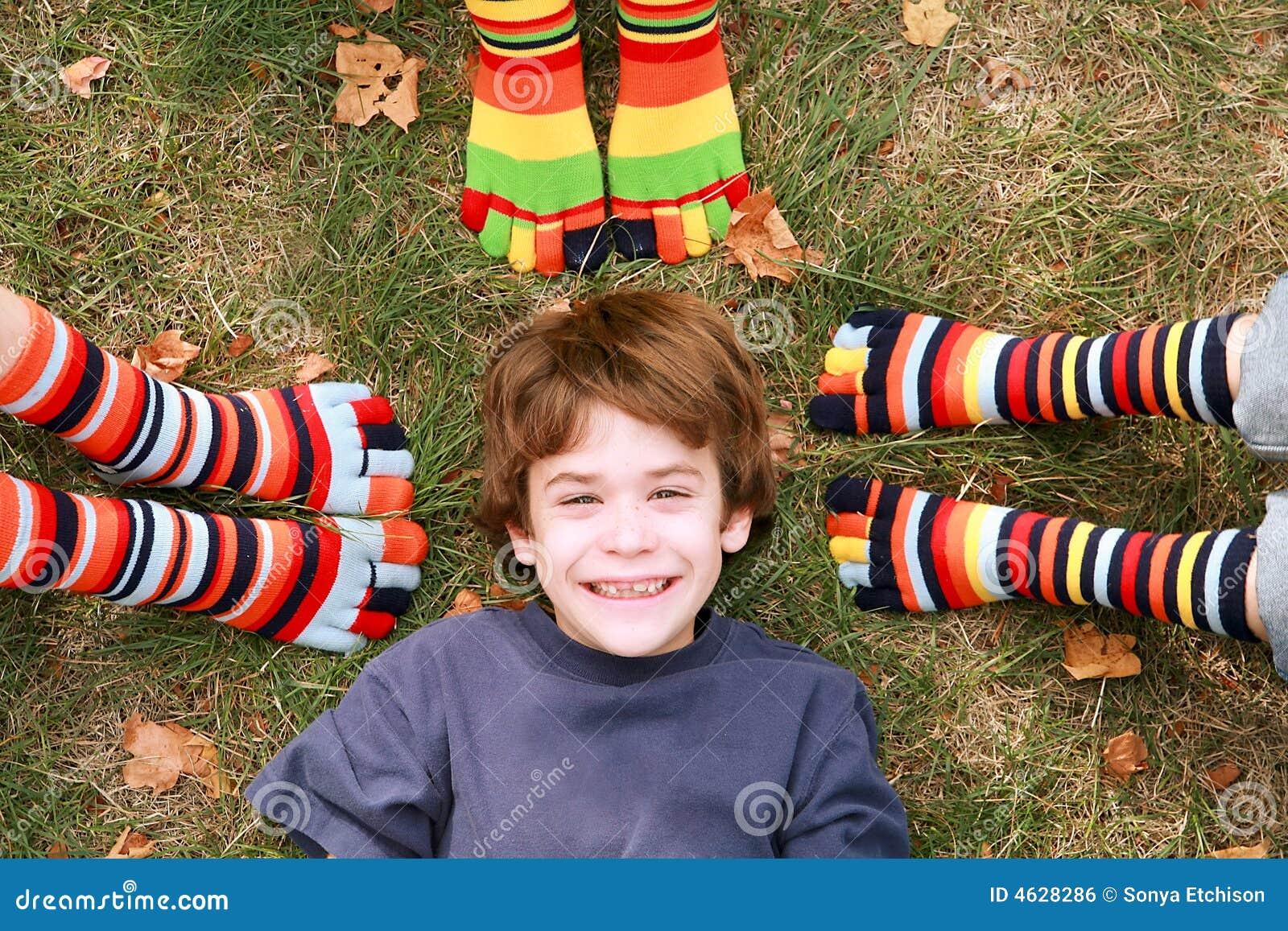 Glimlachen van de jongen Omringd door de Sokken van de Teen