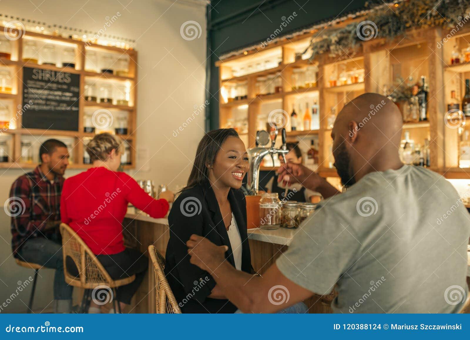 Glimlachend Afrikaans Amerikaans paar dat van dranken samen in een bar geniet