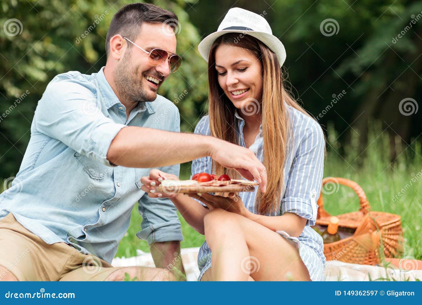 Glimlachend gelukkig jong paar die van hun tijd in een park genieten, die een toevallige romantische picknick hebben