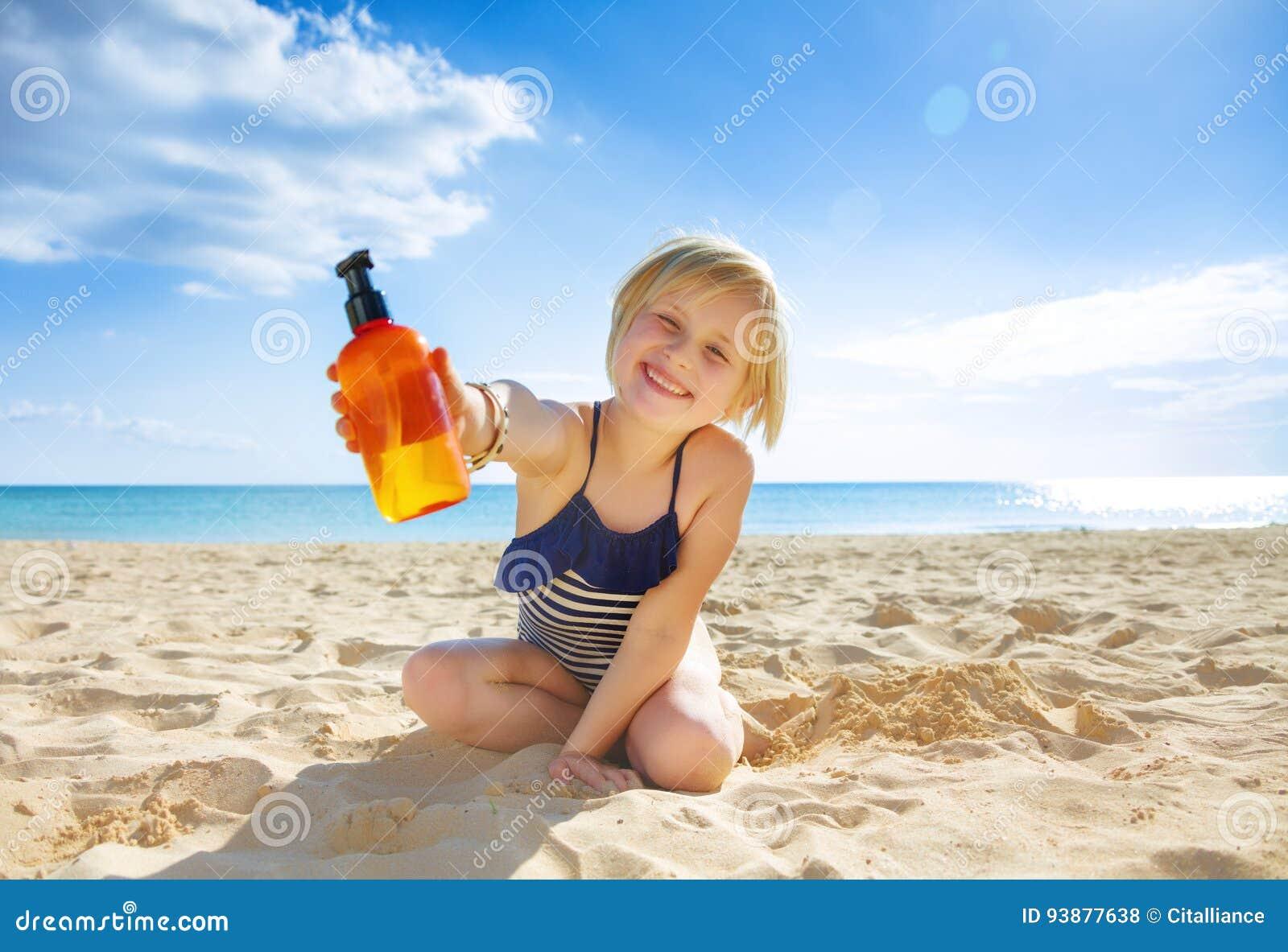 Glimlachend gezond kind in swimwear op zeekust die lotion tonen