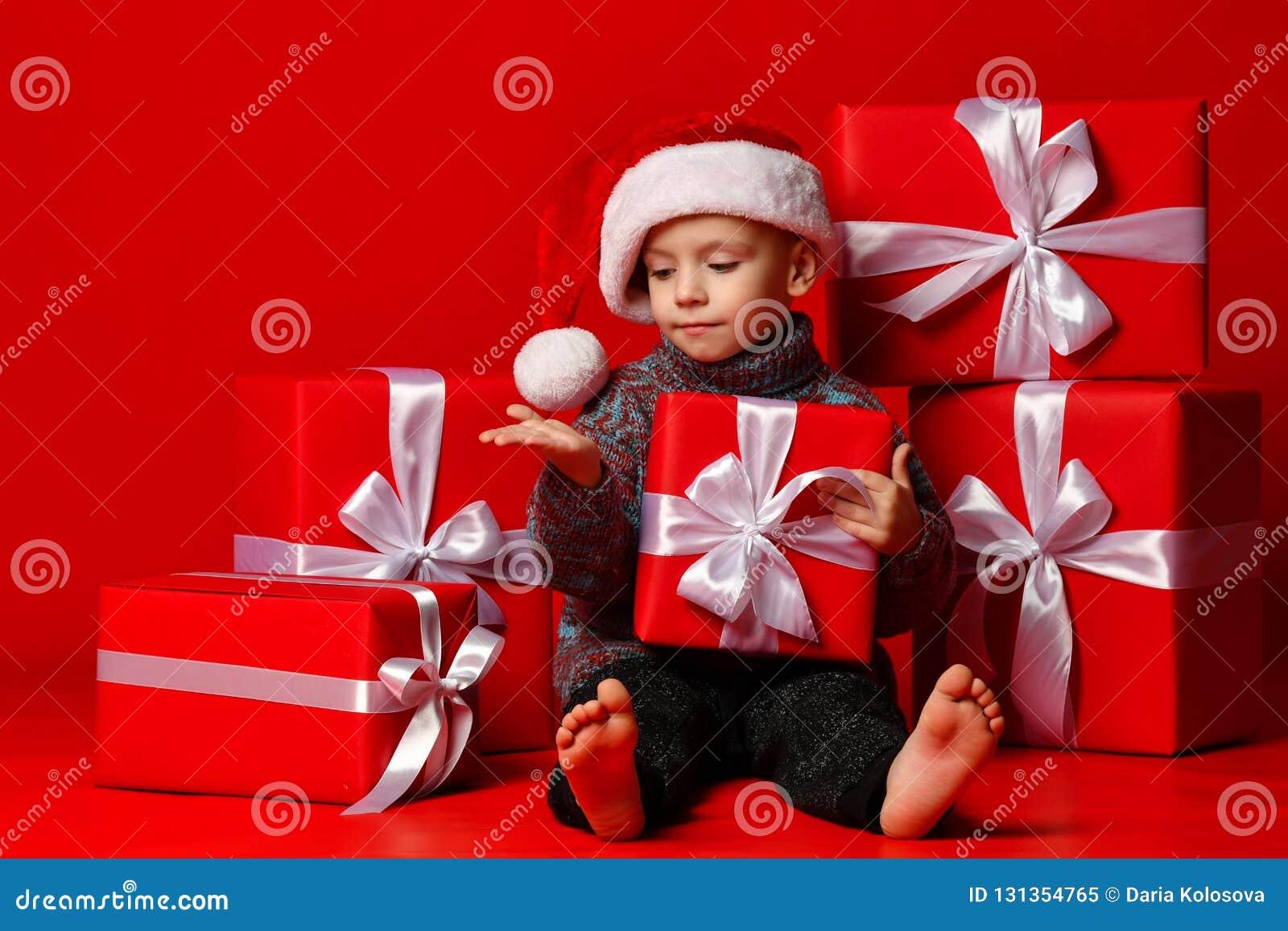 Glimlachend grappig kind in gift van de holdingskerstmis van de Kerstman de rode hoed ter beschikking Kerstmistak en klokken