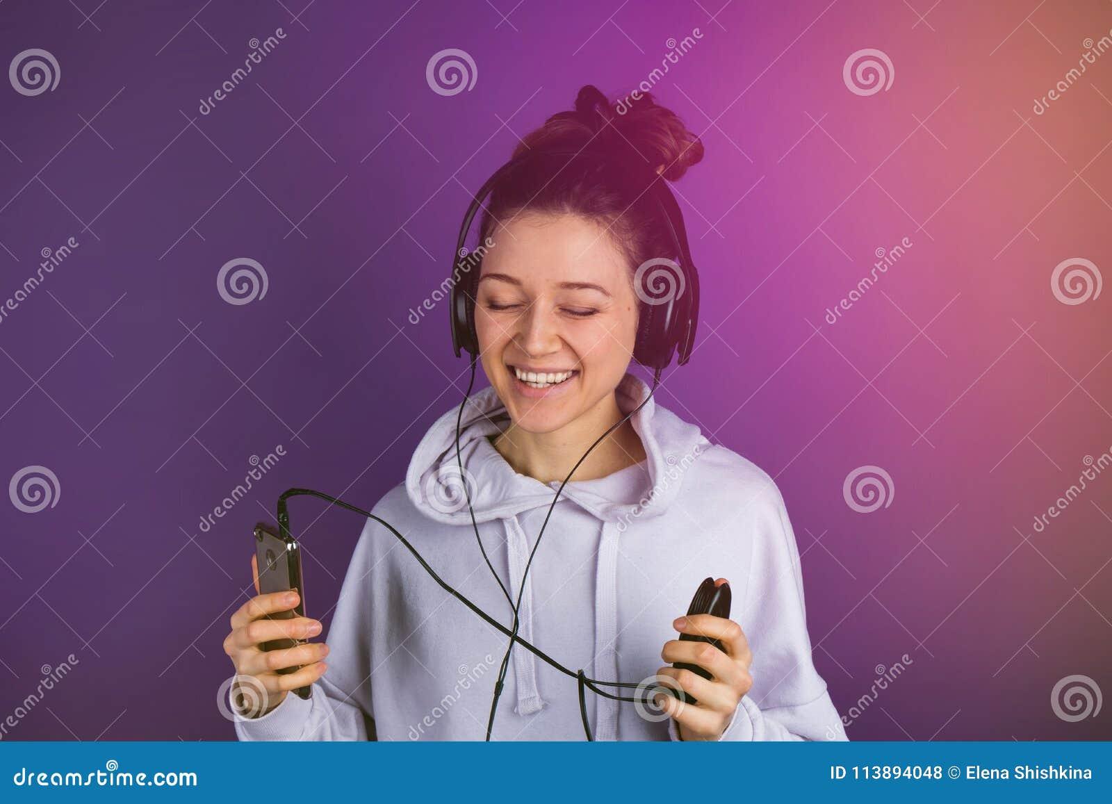 Glimlachend jong mooi meisje die met witte tanden aan muziek op de telefoon luisteren die hoofdtelefoons in een sweatshirt op a d