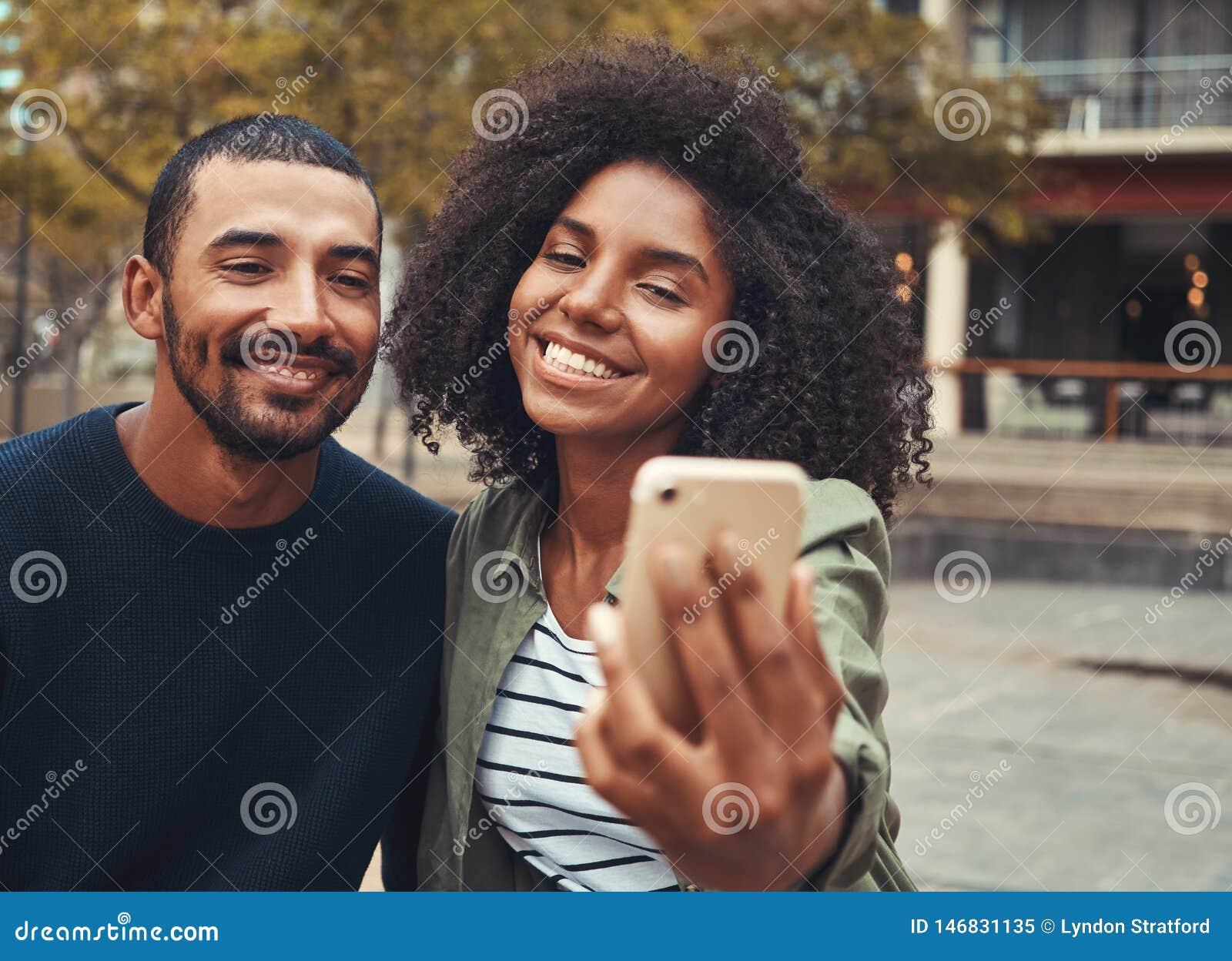 Glimlachend jong paar die selfie op smartphone nemen