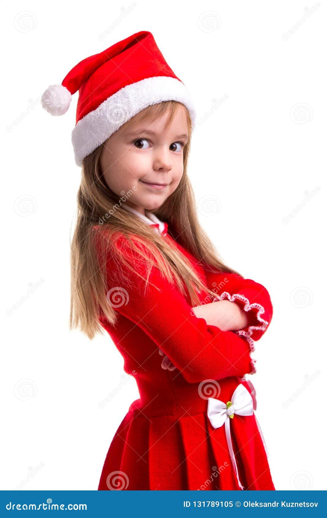 Glimlachend koket Kerstmismeisje die die een santahoed dragen over een witte achtergrond wordt geïsoleerd, die zich in de halve d