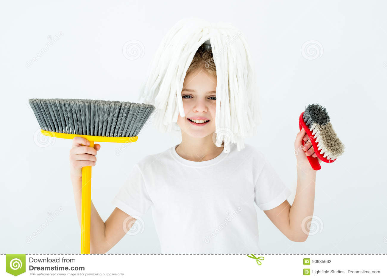 Glimlachend meisje die diverse schoonmakende levering op wit houden