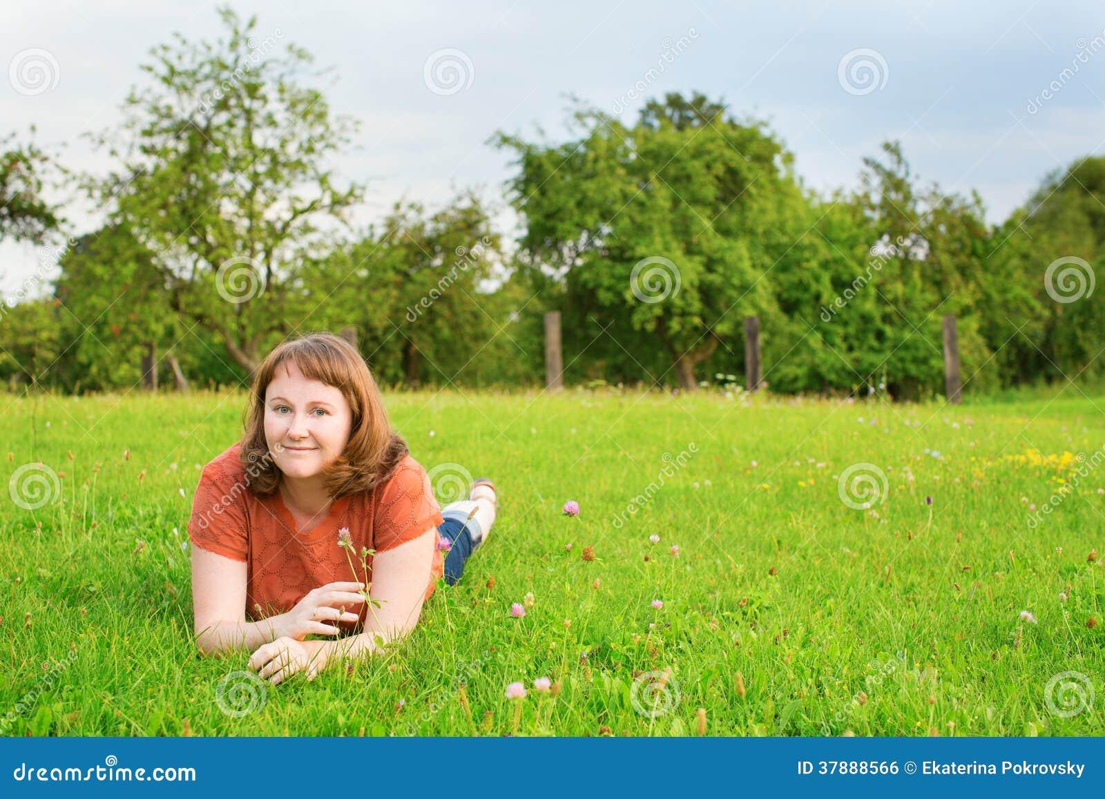 Glimlachend meisje die op gras op een de zomerdag liggen
