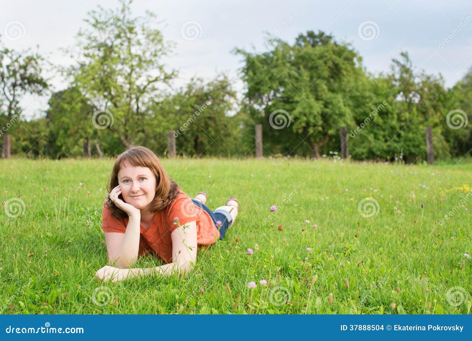 Glimlachend meisje die op het gras liggen