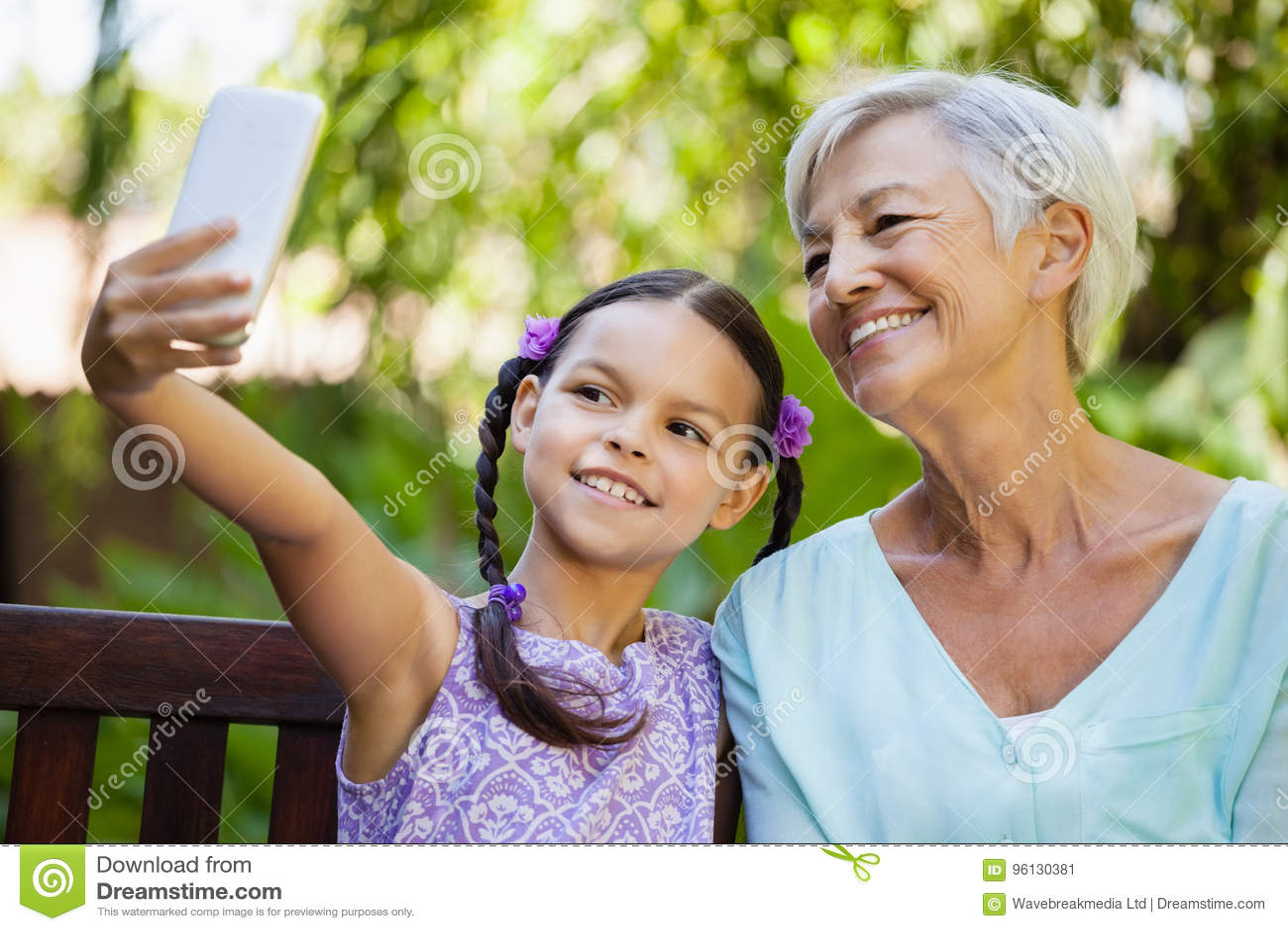 Glimlachend meisje die selfie met grootmoeder nemen