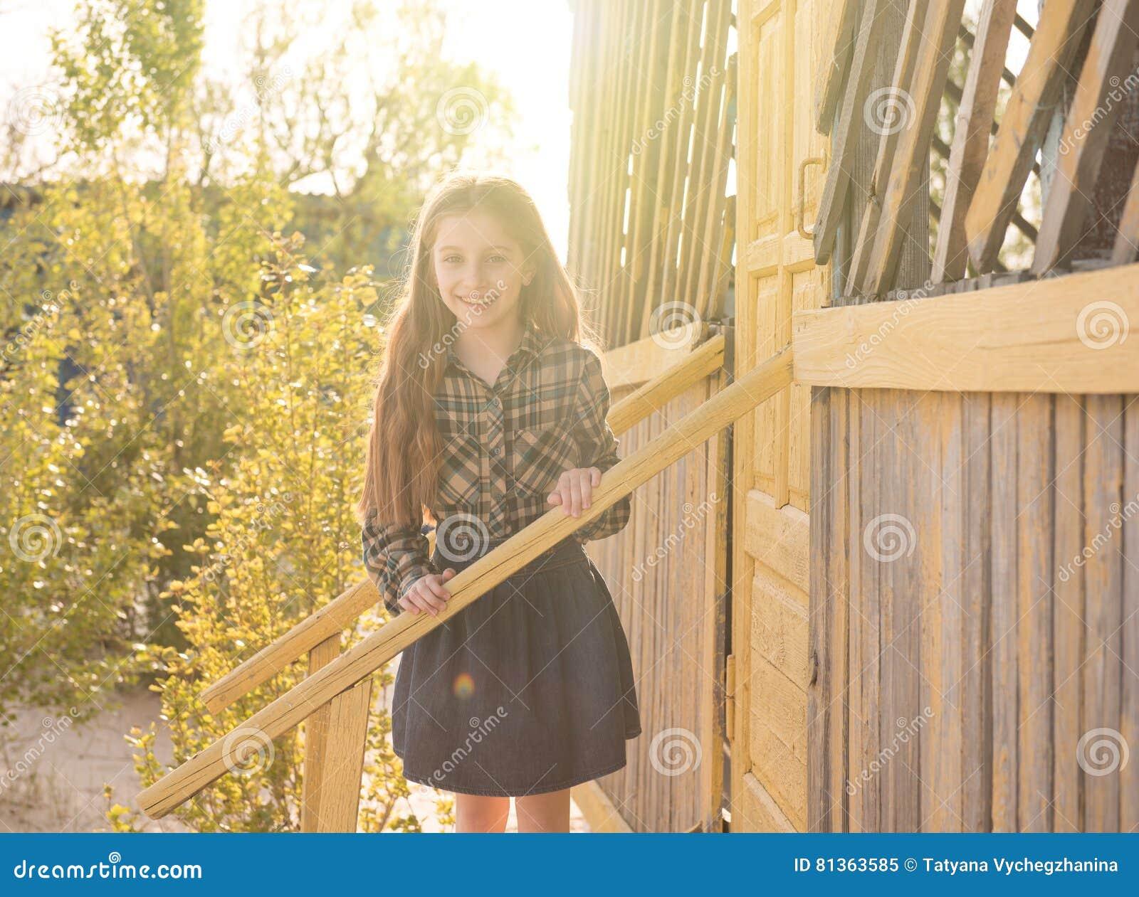 Glimlachend meisje op houten portiek