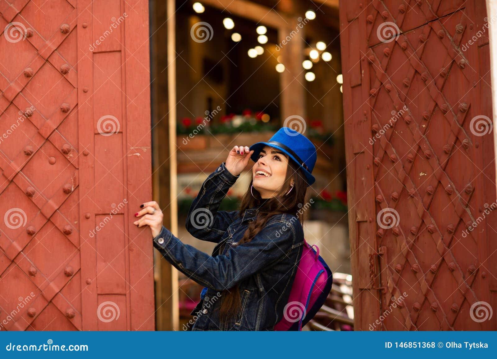 Glimlachend mooi meisje in blauwe hoed dichtbij de oude bouw met antieke rode deuren Het vrouwelijke model stellen