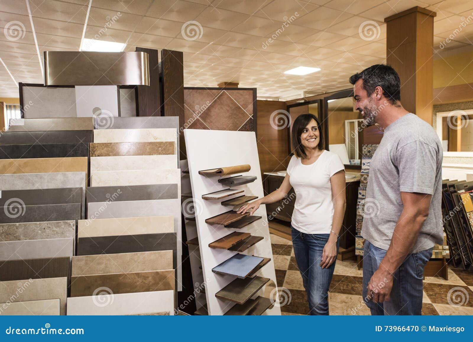 Glimlachend paar die tegel in de opslag van de huisdecoratie kiezen