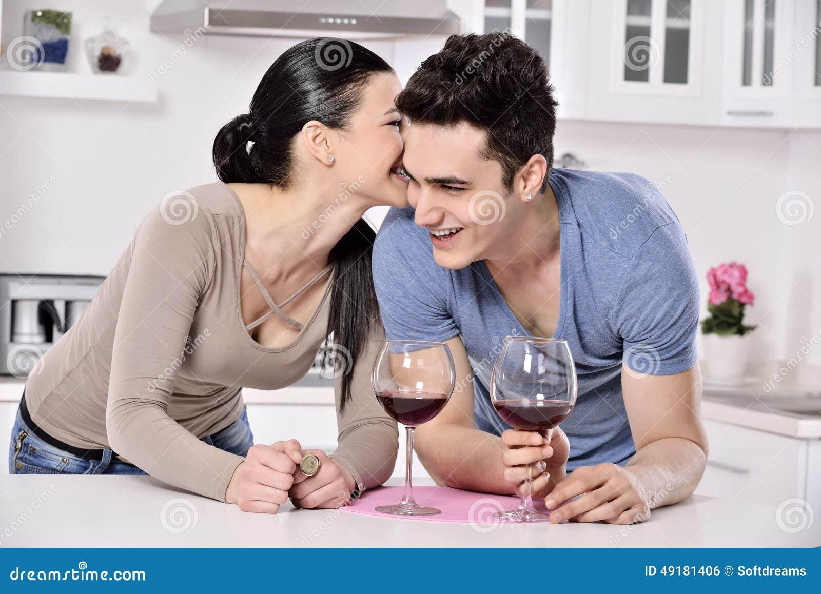 Glimlachend paar die van rode wijnstok in kitchev genieten