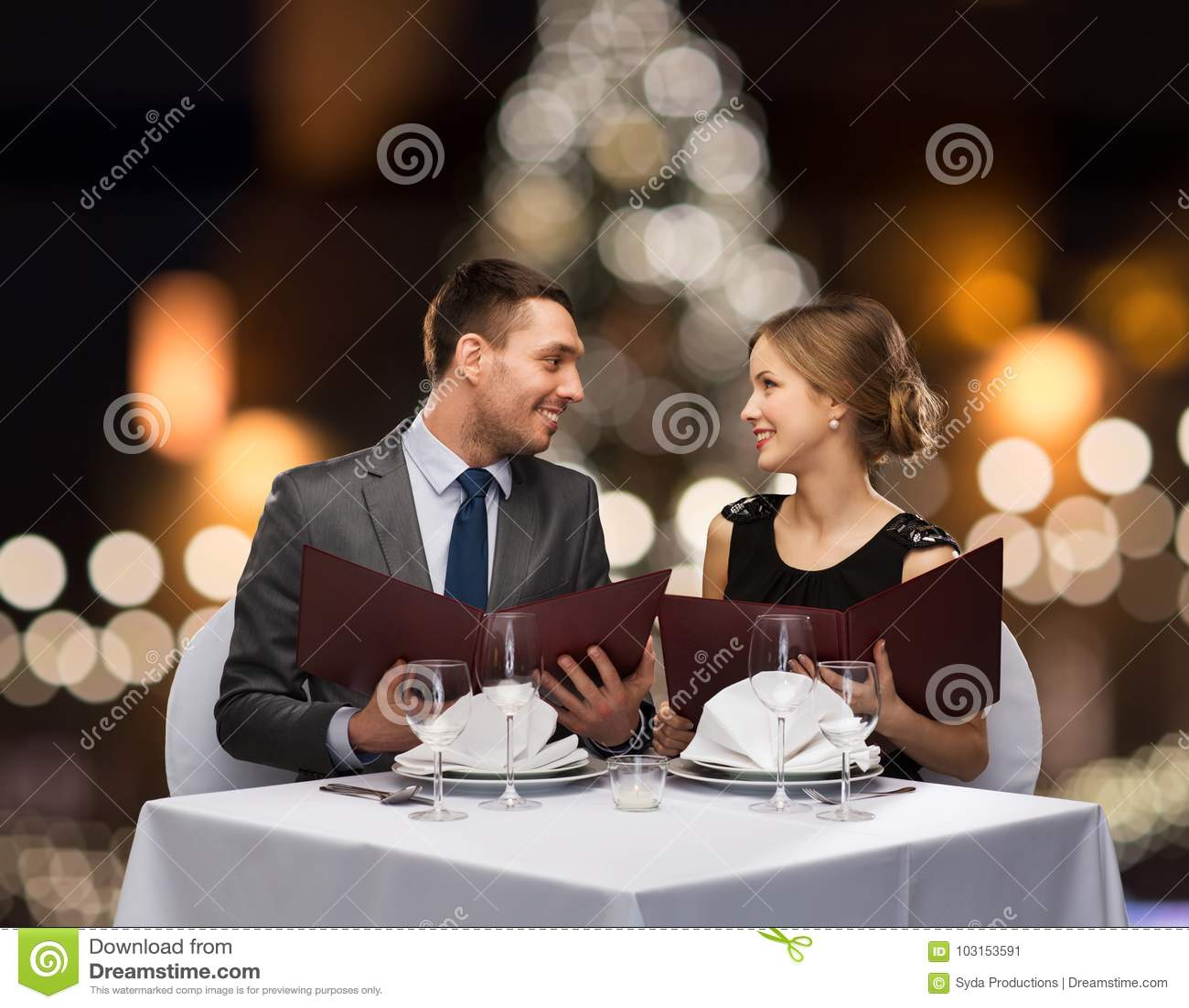 Glimlachend paar met menu s bij Kerstmisrestaurant