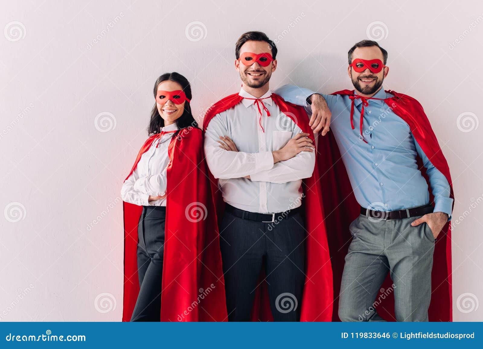 Glimlachend super zakenlui in maskers en kaap die camera bekijken