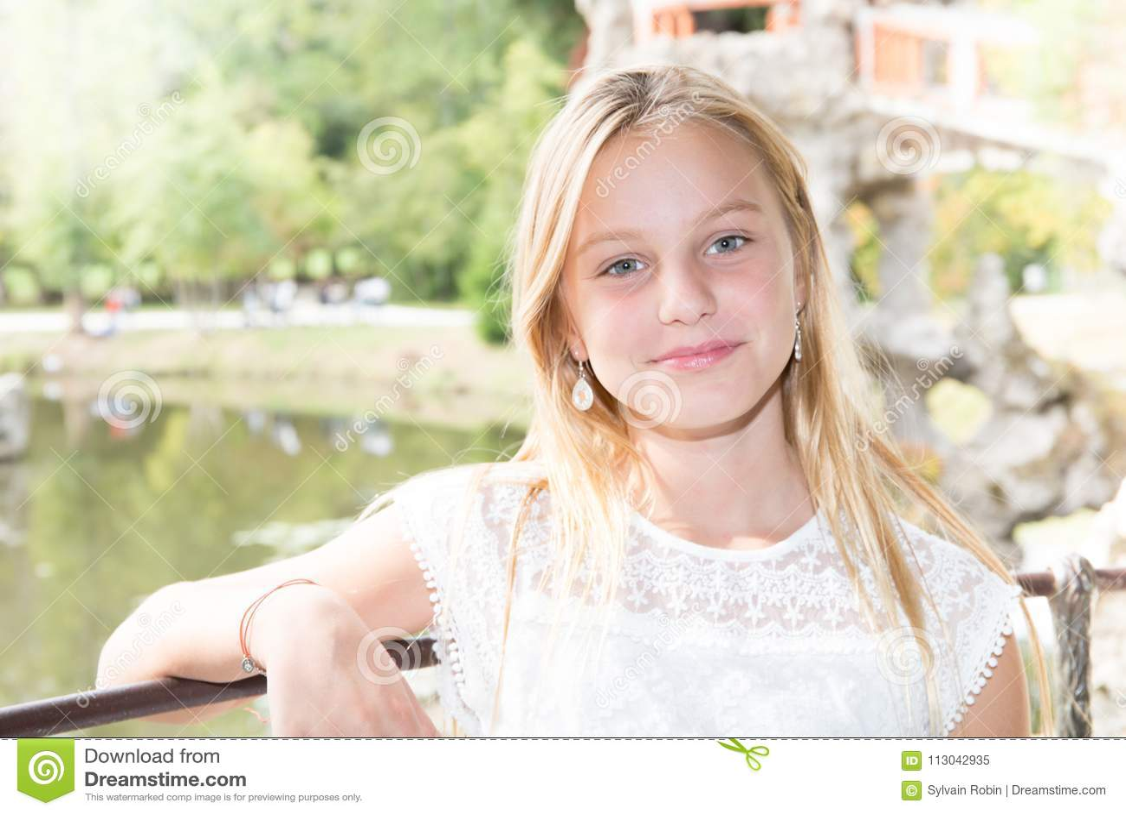Glimlachend tienerblondemeisje tegen meer van de zomerpark