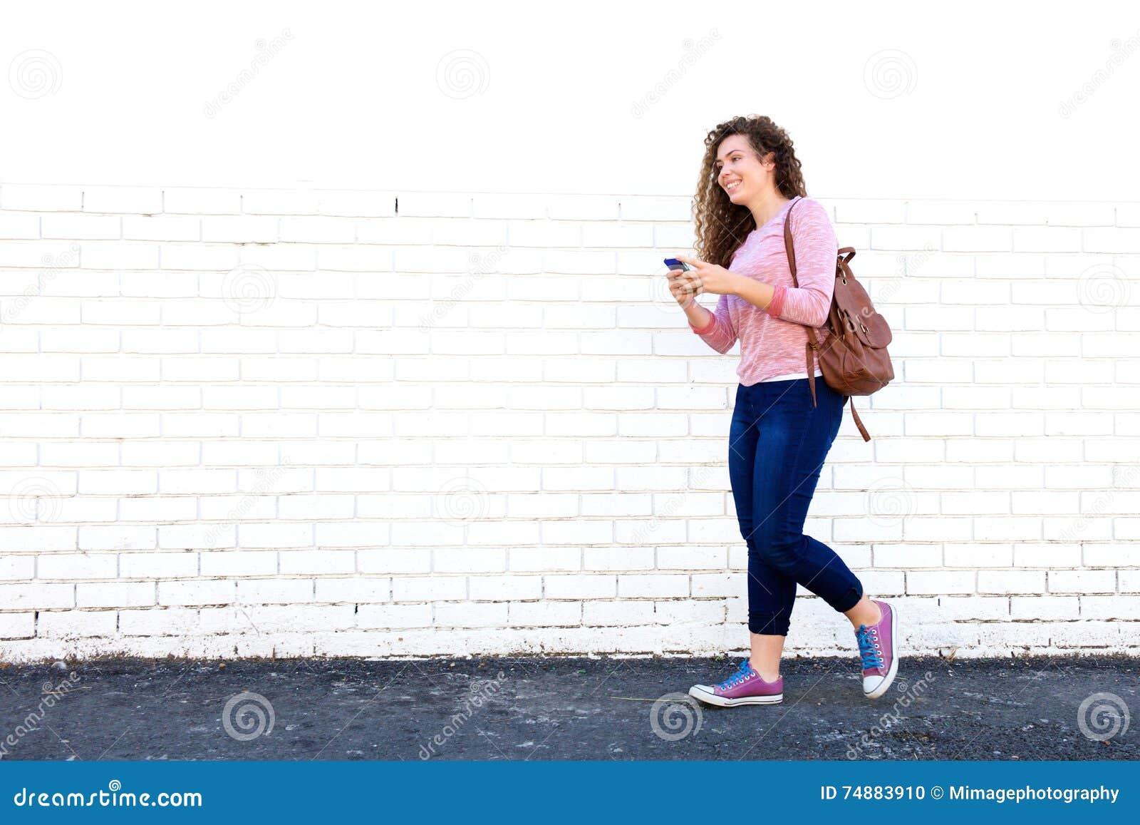 Glimlachend tienermeisje die met cellphone en rugzak lopen