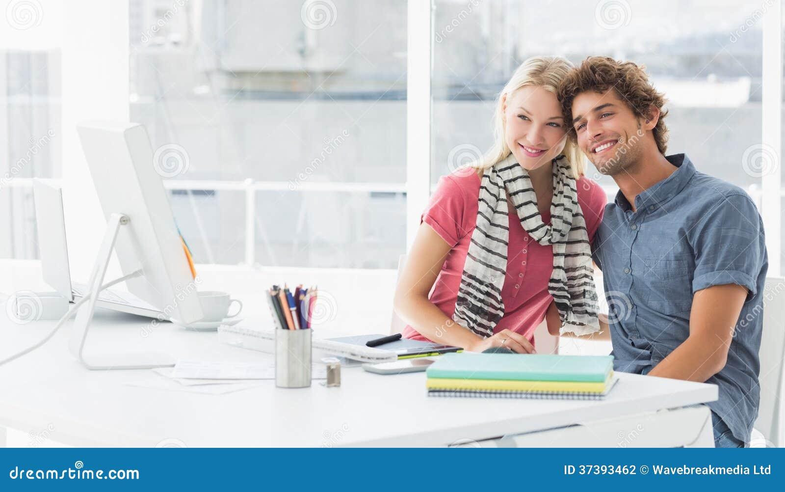 Glimlachend toevallig bedrijfspaar in een helder bureau